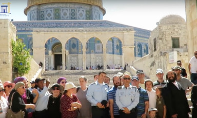 Three Israeli police are seen standing with group of civilians in front of stairs leading up to the Dome of the Rock