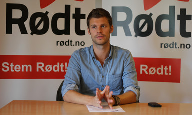 Young man speaks while sitting at desk with a Rødt party banner behind him