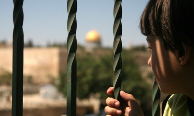 A Palestinian boy looks at the Dome of the Rock mosque as Israeli police blocks the access to al-Aqsa Mosque, outside the Old City walls in East Jerusalem.