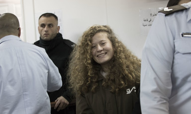 Ahed Tamimi, wearing prison uniform, smiles while surrounded by police