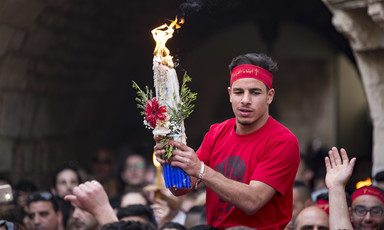 Palestinian Christian worshiper carrying a flame among the crowd.
