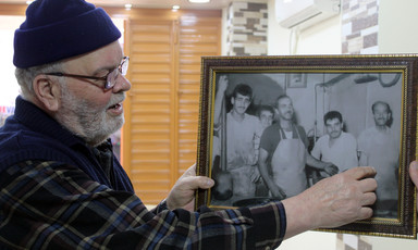 Man in wool hat looks at framed photo he is holding up
