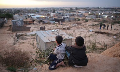 Two boys sit on a sand embankment overlooking a village of corrugated metal shelters