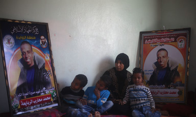 Woman and three small children sit on floor next to two large posters of smiling young man