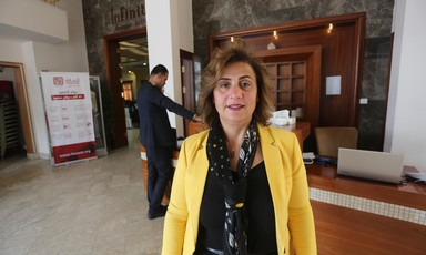 Mona Adnan Ghalayini stands in front of reception desk