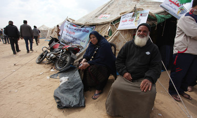 Elderly man and woman sit in front of tent adorned with banner stating We are here to return to our lands