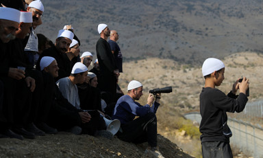 A group of men and boys wearing traditional white caps stand and sit on hillside looking over boundary fence, some holding binoculars