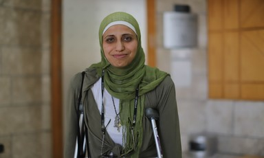 Dareen Tatour stands in court on crutches.