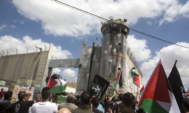 Dozens of protesters carrying Palestinian flags near the apartheid wall.