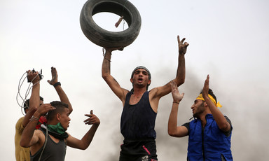 Young man holds tire above his head as other protesters clap and celebrate around him