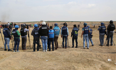 Palestinian journalists wearing press vests stand in a row at the Gaza march.