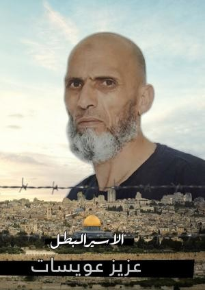 "A poster of Aziz Awisat that says ""Hero prisoner, Aziz Awisat"" with a picture of him above the Jerusalem landscape."