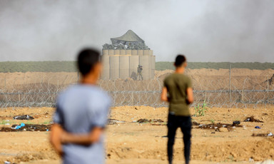 The backs of two standing youth are seen in foreground of photo with Israeli military installation behind barbed wire and fencing in background