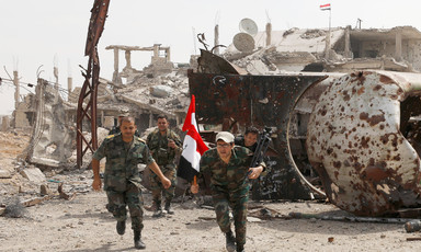 Men in military uniform carry Syrian flag amid rubble of bombed-out buildings