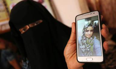 Woman wearing niqab displays photo of adolescent girl wearing a hijab on a mobile phone