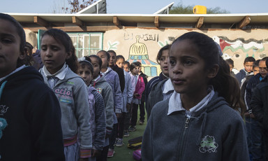 Schoolchildren stand in rows in front of single-story school