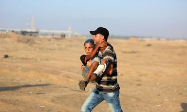 A man carries a boy with a bandaged leg across a sandy landscape
