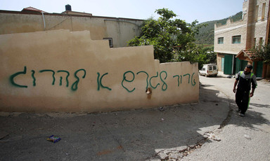 A Palestinian man stands next to a house vandalized with Hebrew-language graffiti.