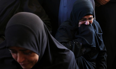 Photo shows two mourning women wearing black headscarves and dresses