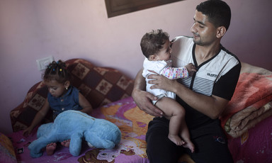 Muhammad al-Najjar smiles and looks at his infant daughter who he is holding while his toddler daughter sits on couch behind him