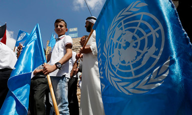Man and boy are seen from legs up holding UN flags