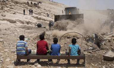 Palestinian children watching an Israeli bulldozer