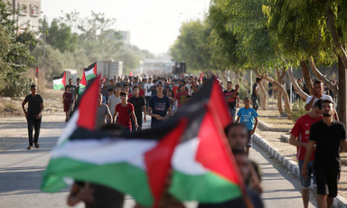 Palestinian men and boys march down street while carrying Palestinian flags