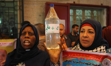 "Palestinian women holding up a bottle reading ""water and salt."""