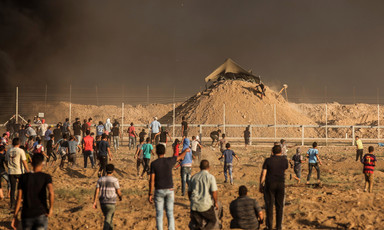 Men and boys stand or run in front of the Gaza boundary fence with an Israeli military installation on a sand hill behind it