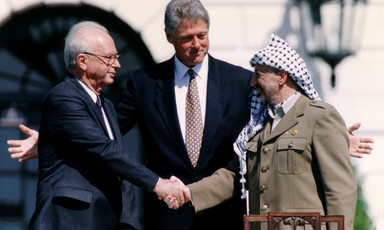 Photo shows Yitzhak Rabin and Yasser Arafat shaking hands while Bill Clinton extends his arms behind them
