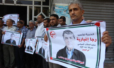 Palestinians hold pictures of Raja Eghbaria