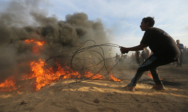 A youth pulls on a barbed wire fence that is partially set on fire as a crowd looks on