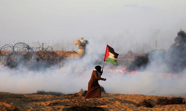 A running woman carries a Palestinian flag as a cloud of smoke emanates from the ground between her and the Gaza-Israel boundary fence