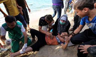 Men and women provide first-aid to a child lying on the beach with a bandage on his leg