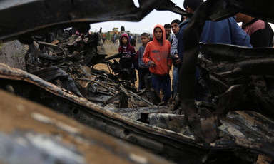 Boys look at wreckage of burned-out vehicle