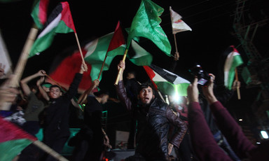 Young men wave the national flag and the Hamas flag at night