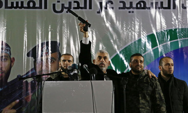 Yahya Sinwar stands behind a podium flanked by two security guards while holding a pistol in the air