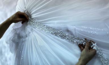 A designer puts the final touches to a wedding dress.