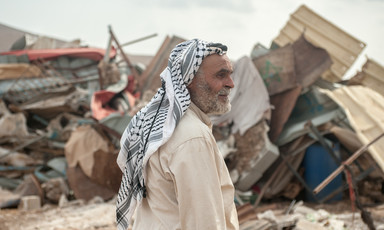Omar Arif Bisharat stands in front of the rubble of his home in al-Hadidiya.