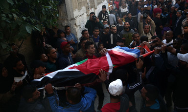 The body of Muhammad Habali, wrapped in a Palestine flag, is carried on a stretcher by crowd in alley