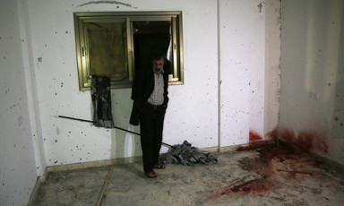 A man stands in front of a window in a room with bullet holes in the walls and a large blood stain in one corner