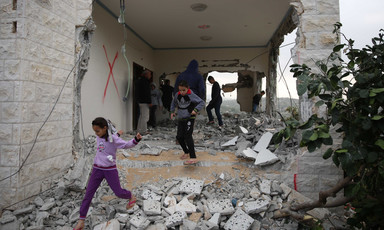 A girl and boy walk through the debris of a building with destroyed walls