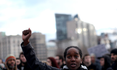 Black person raises fist in air during protest