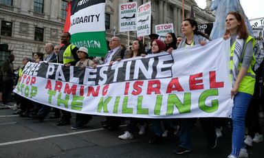 "Marching near the British Parliament, protesters hold a large banner that says ""Free Palestine, Stop Arming Israel, Stop the Killing"""