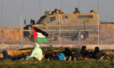 Youths, one holding a Palestine flag, crouch behind a sand embankment with a fence separating them from an Israeli military vehicle and soldiers
