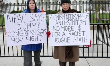 "Protesters stand in front of the White House with signs reading ""AIPAC says jump! Congress says how high?"" and ""Zionism needs/feeds anti-Semitism, no more $ for a rogue racist state"""