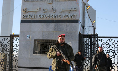 Men in military uniform carrying rifles stand in front of Rafah crossing gate