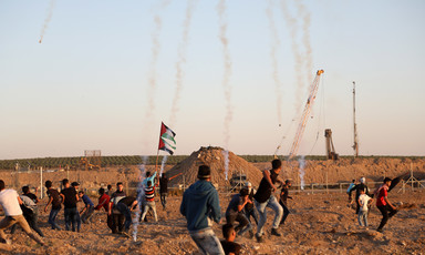 Palestinians protest in front of Gaza boundary fence with trails of tear gas smoke in the sky