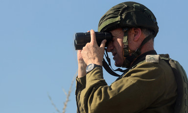 A man in military uniform looks through binoculars