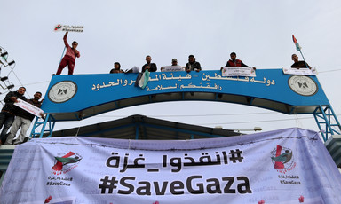 Banner reading #SaveGaza in English and Arabic hangs across checkpoint gate